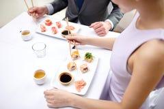 Stäng sig upp av par som äter sushi på restaurangen Arkivbilder