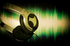 Stäng sig upp headphonen, hörluren som hängs på skärmbakgrund för solid våg Arkivfoton
