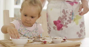 Stäng sig upp på flickaportion för att förbereda muffin Fotografering för Bildbyråer