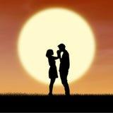 Stäng sig upp romantiska par vid solnedgångsilhouetten Arkivbilder