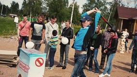 Stoß des jungen Mannes mit Kraft auf empfindlichem aufblasbarem stehen Schmiedehammer bereit Sommerfestival stock video