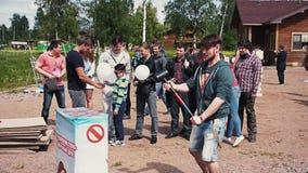 Stoß des jungen Mannes mit Kraft auf empfindlichem stehen Schmiedehammer bereit Sommer Fest Park stock footage