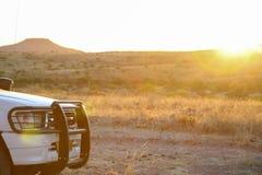 Stoßdämpfer von 4x4 SUV mit Berg und Sonnenuntergang im Hintergrund, Stockbild