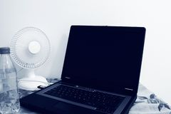 Stołowego fan stojaki obok laptopu i plastikowej butelki wypełniali z wodą zdjęcie stock
