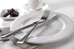 Stołowy położenie nóż, rozwidlenie na porcelana talerzu, bieliźnianym płótnie, pucharze czekolada kawałki i filiżance z spodeczki zdjęcia stock