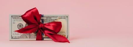 Sto dolarów prezentów wraped z czerwonym faborkiem na różowym tle zdjęcie stock