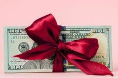 Sto dolar?w prezent?w wraped z czerwonym faborkiem na r??owym tle fotografia stock