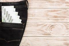 Sto euro banknotów w cajgi wkładać do kieszeni na białym drewnianym tle z kopii przestrzenią dla twój teksta Odgórny widok Obrazy Stock
