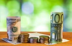 Sto euro i sto dolary amerykańscy staczających się rachunków banknotów Zdjęcia Stock
