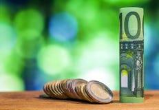 Sto euro staczał się rachunku banknot z euro monetami na zieleni, Zdjęcia Stock