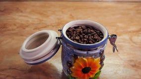 Stoccaggio dei chicchi di caffè Contenitore ceramico con caffè Nave ermetica con i grani di caffè arrostito Sul tavolo da cucina video d archivio
