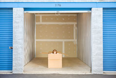 Stoccaggio: Donna che dà una occhiata per parteggiare dalla scatola nell'unità Fotografia Stock