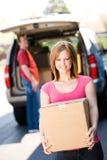 Stoccaggio: La donna porta la scatola dal camion Fotografia Stock