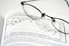 Stock analysis. With graph and glasses Stock Photos
