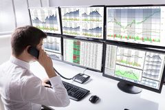 Close-up Of Stock Broker Talking On Telephone. Stock Broker Talking On Telephone In Front Of Multiple Computer Screen Showing Graphs Royalty Free Stock Photos