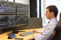 Stock broker trading online. Stock broker trading online while accepting orders by phone. Trader`s office with multiple computer screens full of index charts Stock Images
