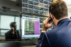 Stock broker trading online, talking on mobile phone. stock photo