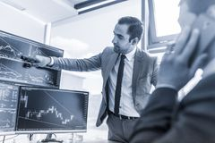 Stock brokers trading online in corporate office. Stock Photo
