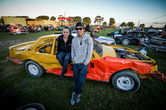 Stock car racing. A young couple stand beside their stock car at a speedway track near Napier, New Zealand Stock Photography