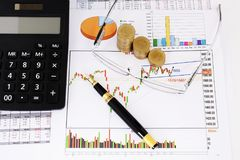 Stock chart concept with fountain pen and eyeglasses and coins stack and calculator stock image