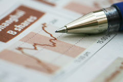 Stock Chart with pen. On newspaper Stock Image