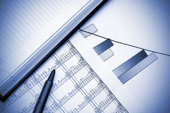 Stock chart, pen and notebook. Blue toned Royalty Free Stock Photography