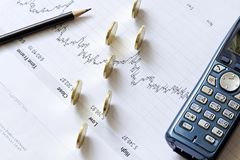 Stock chart with a pencil, a telephone and coins Stock Images