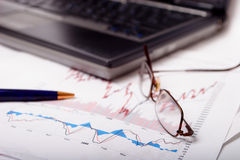 Stock charts with laptop and shallow dof. Stock charts with pen and glasses with shallow dof. Also available with blue overlay. See my other finance related royalty free stock images
