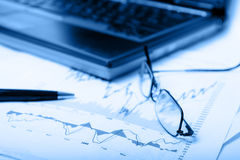 Stock charts w blue and shallow dof. Stock charts with pen and glasses with shallow dof. See my other finance related pictures with or without the blue overlay royalty free stock image