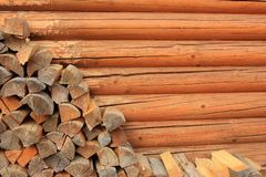 Stock of chipped firewood along wooden sauna wall with copy space. Wood background. Stack of firewood as preparing to winter. Stocking for winter Royalty Free Stock Photo