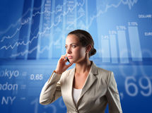 Stock exchange. Businesswoman talking to telephone with stock exchange graphics on the background