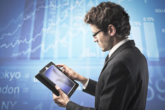 Stock exchange. Young businessman usinga  tablet pc with stock exchange graphics in the background Stock Photo