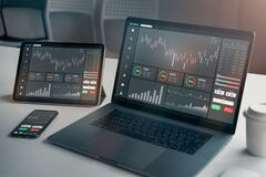 Stock exchange market concept, laptop and tablet, smartphone on the table with graphs analysis candle line in office room