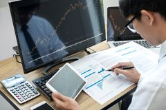 Stock exchange market concept, stock broker looking at graph working and analyzing with display screen, pointing on the data. Presented and deal on a exchange royalty free stock photo