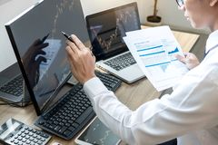 Stock exchange market concept, stock broker looking at graph working and analyzing with display screen, pointing on the data. Presented and deal on a exchange royalty free stock photography