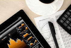 Stock exchange workplace. Desktop in stock exchange office with a tablet pc showing stock market chart Royalty Free Stock Images