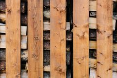 Stock of firewood for the winter. Siberian Village. Wooden fence with firewood royalty free stock photography