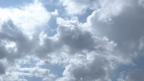 Clouds moving slowly. This stock footage features a close-up shot of  clouds moving in slow motion beneath the bright sun and the blue sky. The sunlight is stock video footage