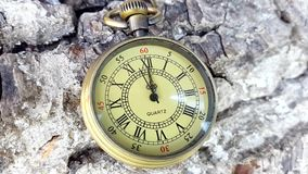 Golden Pocket Clock. This stock footage features a golden pocket clock lying on rough terrain. The clock says the time is 12 o`clock. Use this video in stock video