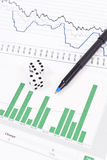 Stock Gamble. Dice on Stock Market Graphs and Pen Stock Photo