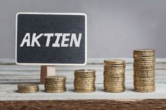 Stock in German language on sign. Aktien Stock in German language, white chalk type on black board, Euro money coin stacks of growth on wood table royalty free stock image