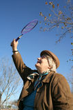Stock image of badminton game. Happy grandmother wearing peaked cap and glasses playing badminton in city park on beautiful sunny autumn day stock photos