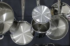 Stainless steel pots and pans hanging in the kitchen. Stock image of luxury stainless steel pots and pans hung in a kitchen interior reflective metal Royalty Free Stock Photo