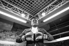 Businessman with boxing gloves ready corporate battle. Stock image of person wearing business suit and boxing gloves. African man in a classic suit and Boxing Stock Photography