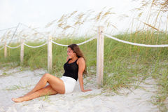 Stock image of a woman sitting by the dunes Stock Photo