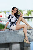 Stock image of a woman sitting on a marina ledge Royalty Free Stock Image