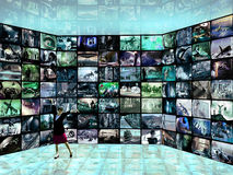 Stock images. Multiple tv screens, with photos and illustrations, presented by a young cute woman royalty free stock images