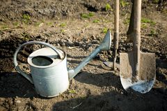 Stock in kitchen garden. A watering can, a  spade and a  mattock on the ground in a peasant's kitchen garden Stock Image