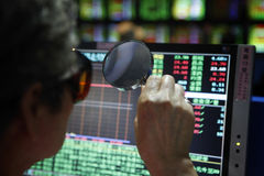 Stock market. The index of Taiwan's stock market rise 75.81 points on May. 27, 2010. A investor hold a magnifier to see the index Stock Photos