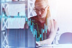 Stock market and accounting concept. Attractive european businesswoman using laptop in modern office with forex chart. Stock market and accounting concept stock photography